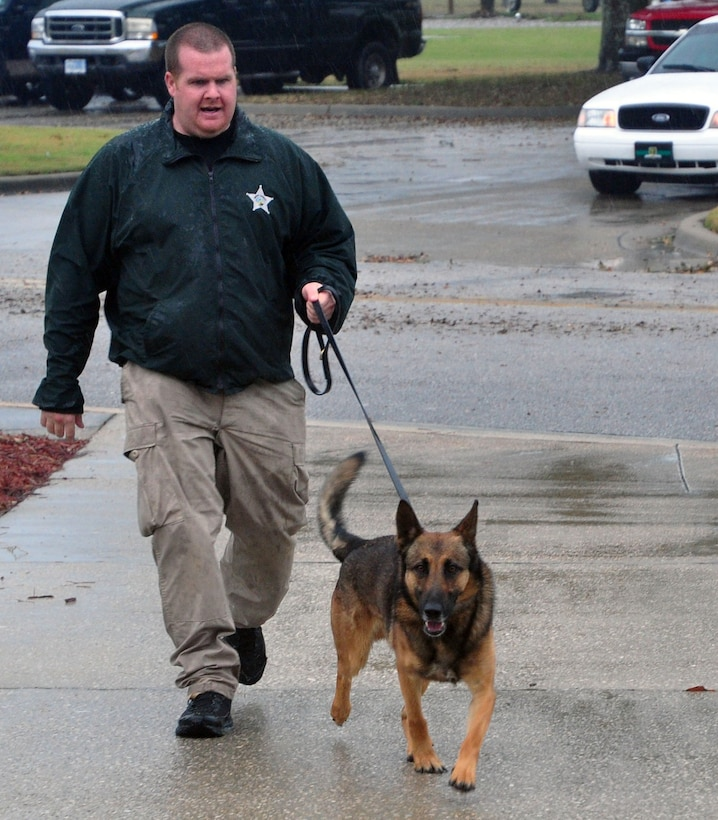 Andrew Longo, Washington County Sheriff's Office deputy, leads Risko, his canine companion, into the Tyndall base chapel Feb. 7 as part of a narcotics working dog seminar attended by local and base authorities. (U.S. Air Force photo by Airman 1st Class Alex Echols)