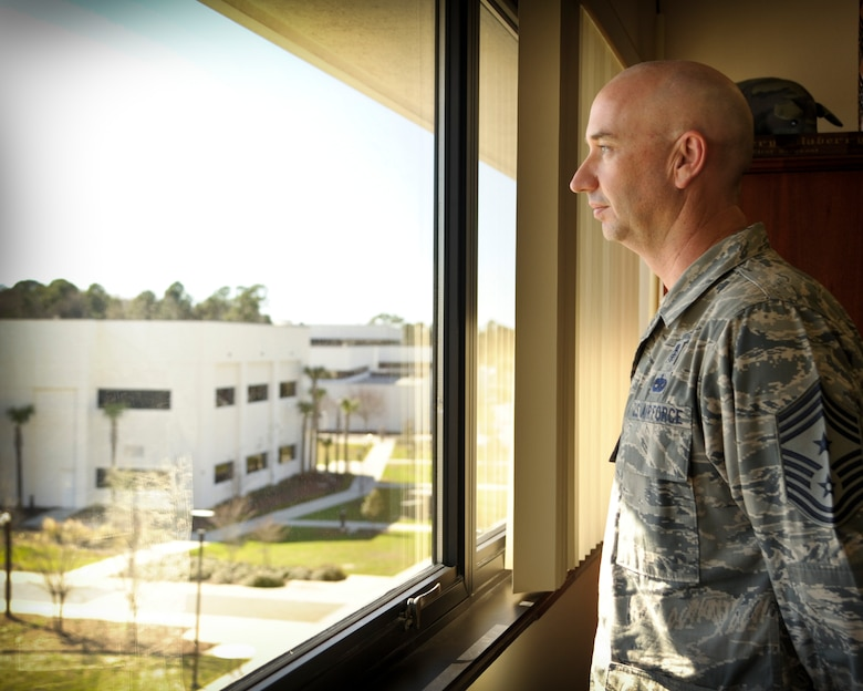 """Chief Master Sgt. Jeffery Maberry, command chief of 1st Special Operations Wing gazes out his office window upon the base at Hurlburt field, Fla., Feb. 7, 2013.  Throughout his 25-year career as an enlisted member of the Air Force, Maberry held a broad spectrum of jobs and positions that ultimately guided his path to becoming a command chief of 1 SOW.  Maberry is no stranger to working closely with Airmen, as a third or more of his career has been spent as a first sergeant, always carrying his mantra, """"know your Airmen."""" (U.S. Air Force photo/Senior Airman Krystal Garrett)"""