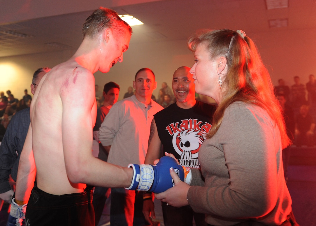 "Col. DeAnna Burt, 460th Operations Group commander, congratulates Rick ""The Reach"" Van Seters after his bout at the Buckley MMA Fight Night Feb. 9, 2013, at Buckley Air Force Base. Van Seters, an Airman with the 460th Space Communications Squadron, lost a three-round battle versus James Nakashima. (U.S. Air Force photo by Senior Airman Marcy Glass/Released)"