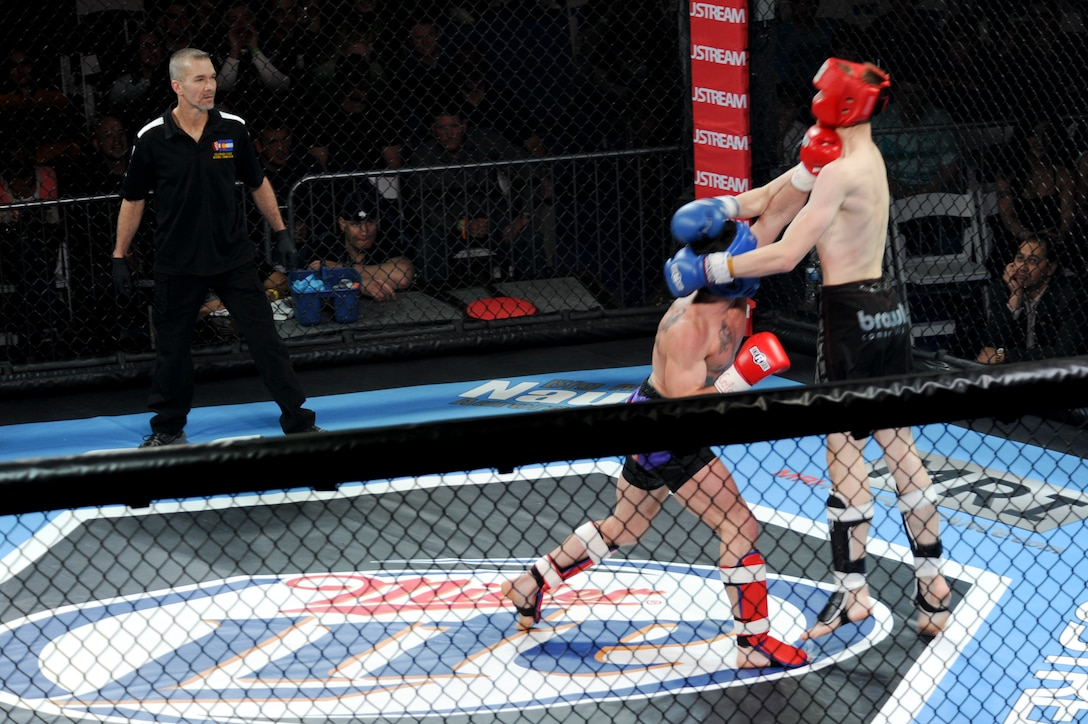 "Rick ""the Reach"" Van Seters receives a punch from James Nakashima during the first fight of the Buckley MMA Fight Night Feb. 9, 2013, at Buckley Air Force base. Van Seters, an Airman from the 460th Space Communications Squadron, fought his debut fight after eight years of training. (U.S. Air Force photo by Airman 1st Class Phillip Houk/Released)"