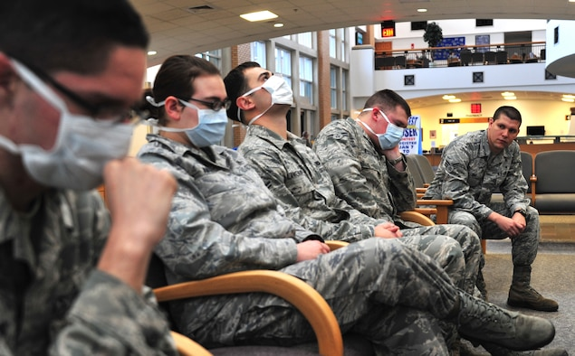In this staged photo, Senior Airman Osniel Diaz, 42nd Medical Group public health professional, peers down a line of sick service members during this flu season. To date, the clinic has issued more than 6,500 influenza vaccines for this season's outbreak. (U.S. Air Force illustration by Senior Airman Christopher Stoltz)