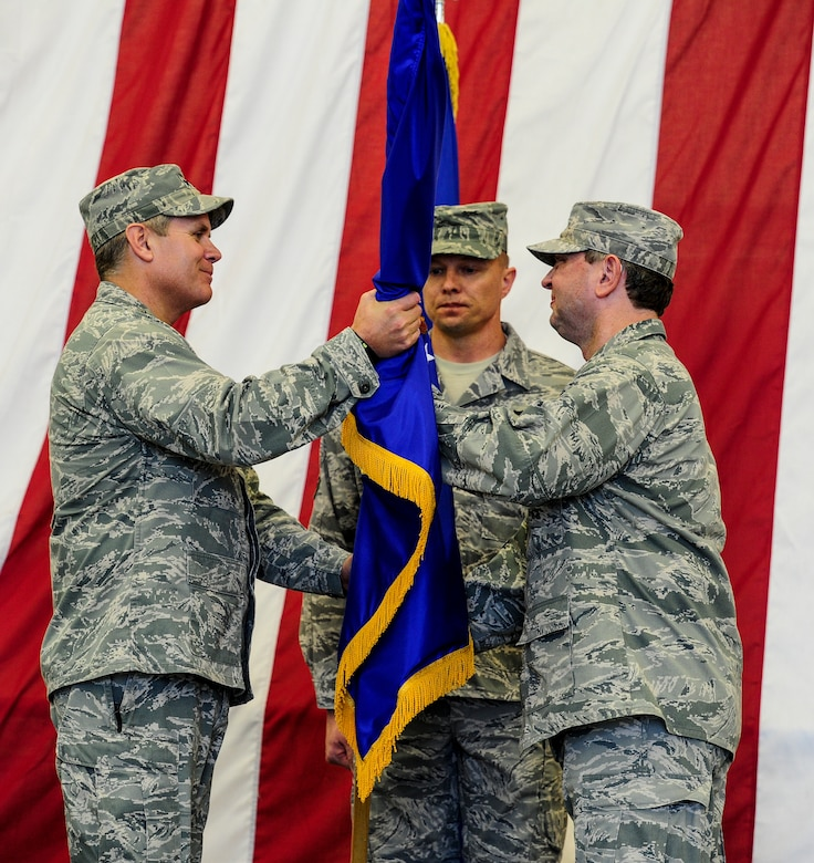 U.S. Air Force Lt. Gen. Eric Fiel, commander of Air Force Special Operations Command, left, takes the Air Force Special Operations Training Center flag from Col. William Andersen, commander of AFSOTC, right, during a ceremony held on Duke Field, Fla., Feb. 11, 2013. The ceremony was held for the deactivation of AFSOTC and the activation and assumption of command of the Air Force Special Operations Air Warfare Center. (U.S. Air Force photo/Airman 1st Class Christopher Callaway)