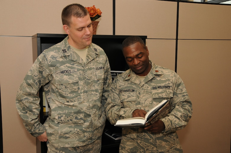 New York Air National Guard Maj. Gary Richardson (right), 174th Attack Wing Equal Opportunity Director and Capt. James Hockey, Equal Opportunity Officer, read a passage from a book on equal opportunity at the Joint Health and Wellness Center on Hancock Field Air National Guard Base, Syracuse, NY February 3, 2013. Richardson is preparing for his job as the Equal Opportunity service liaison for the National Guard Component. (Photo by NY Air National Guard Senior Airman Duane Morgan/Released)