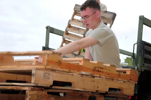 Senior Airman Nicholas Walters, 36th Maintenance Squadron aircraft electrical and environmental systems specialist, stacks pallets during a volunteer event at Andersen Middle School here Feb. 7, 2013. Fifteen Airmen from Team Andersen volunteered to box and palletize more than 400 desks at AMS and send them to the Defense Reutilization and Marketing Office on Naval Base Guam. (U.S. Air Force photo by Senior Airman Robert Hicks/Released)