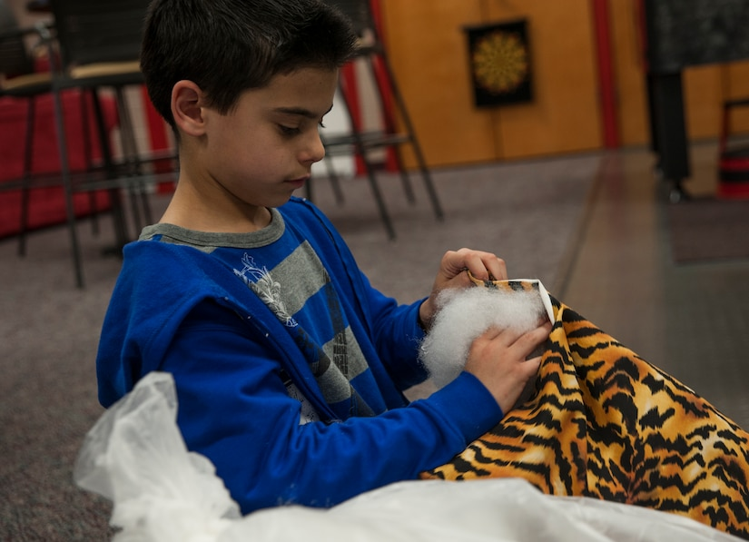 Matthew Hughes, stepson of Sgt. Luis Crovetto, Marine Corps Reserve Unit heavy equipment chief, stuffs a pillow Feb. 12, 2013, at Joint Base Charleston- Air Base Youth Program Center, S.C. 'Pillows for Troops' is an ongoing project at the Youth Program Center, where children ages 9 to 15 are able to make pillows for troops who are deployed overseas. The project takes place every Tuesday through Friday from 3:30 p.m. to 4:30 p.m. (U.S. Air Force photo/Airman 1st Class Ashlee Galloway)