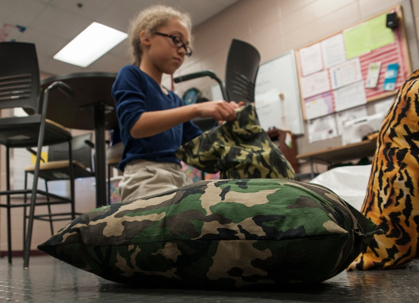 Danyelle Gibson, daughter of Tech. Sgt. Robert Alvarado, 437th Aircraft Maintenance Squadron communications and navigation systems craftsman, stuffs a pillow Feb. 12, 2013, at the Joint Base Charleston- Air Base Youth Program Center. 'Pillows for Troops' is an ongoing project at the Youth Program Center, where children ages 9 to 15 are able to make pillows for troops who are deployed overseas. The project takes place every Tuesday through Friday from 3:30 p.m. to 4:30 p.m. (U.S. Air Force photo/Airman 1st Class Ashlee Galloway)