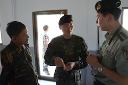 Royal Thai Navy Col. Saniroj Thumayos, the Royal Thai Senior Planner for exercise Cobra Gold 2013 (center) discuses the importance of humanitarian assistance during CG 13 with Burmese Army Maj. Gen. San Myint deputy chief of armed forces training joint warfare training department, (left) and the Peoples Republic of China Capt. Guo Dong Guartgzhou Military Region Interpreter (right). CG 13, in its 32nd iteration, is a multinational exercise that promotes regional prosperity, security and cooperation among partner militaries. (U.S. Army photo by Sgt. Rory Featherston/Released)
