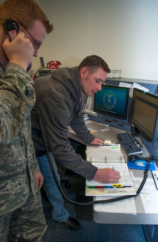 "Tech. Sgt. Jason Brown (right), 507th Air Refueling Wing command post specialist and Staff Sgt. Erik Orr, 137th ARW command post specialist work jointly on a emergency response checklist.  The ""Sooner Control"" command post is the only joint guard and reserve command post with a nuclear mission in the Air Force. (U.S. Air Force Photo by Senior Airman Mark Hybers)"