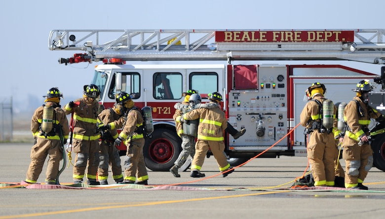 Beale firefighters assist Airman 1st Class Eric Whaley, 9th Civil Engineer Squadron firefighter, to safety during a pilot rescue exercise on the flight-line at Beale Air Force Base, Calif., Feb. 13, 2013. The fire department routinely runs various exercises to stay proficient. (U.S. Air Force photo by Staff Sgt. Robert M. Trujillo/Released)