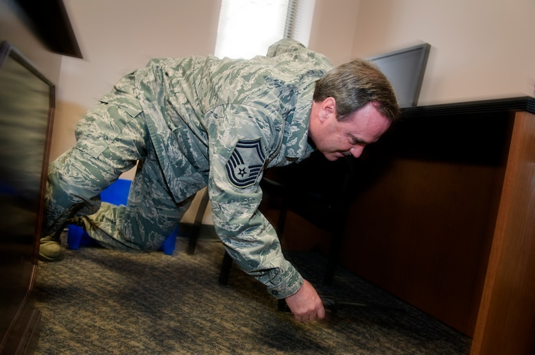 GRISSOM AIR RESERVE BASE, Ind. -- Senior Master Sgt. Joseph Lageose, 434th Maintenance Squadron production superintendent, dives under a desk during an earthquake exercise here Feb. 7. During an earthquake, it is recommended people follow the steps of drop, get under cover and hold on to protect themselves from falling debris. (U.S. Air Force photo illustration/Tech. Sgt. Mark R. W. Orders-Woempner)
