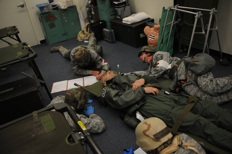 Medics from the 366th Medical Group are forced to move a patient to the ground and continue care Feb. 13, 2013, at Mountain Home Air Force Base, Idaho. Despite hardships and intense working conditions, these personnel provide excellent care to all patients who come through their door during the Sharpshooter 13-2 exercise. (U.S. Air Force photo/Senior Airman Benjamin Sutton)