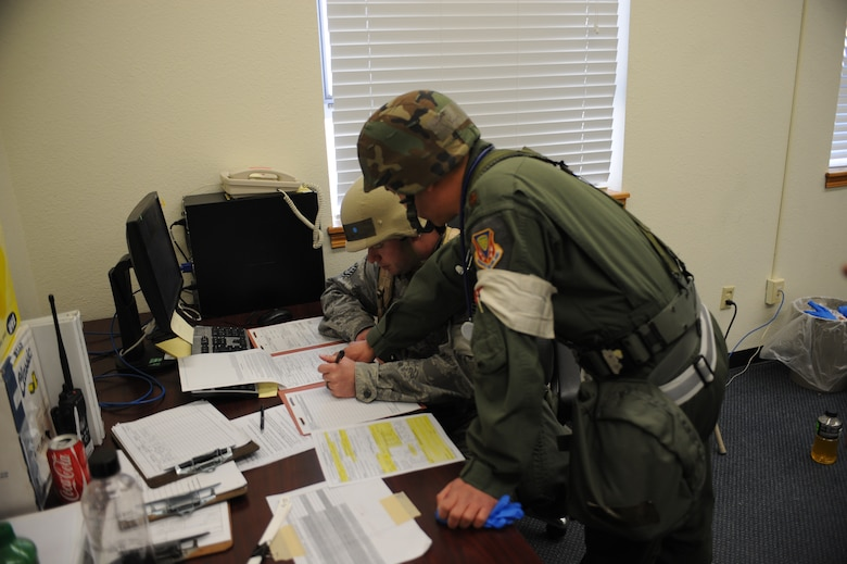 U.S. Air Force Maj. Kevin Loh, 366th Medical Group flight surgeon and Staff Sgt. Michael Montgomery, 366th MDG medic, coordinate a medical evacuation for patients inside the treatment facility Feb. 13, 2013, at Mountain Home Air Force Base, Idaho. Paperwork is extremely important and must be filled out correctly in order to ensure mission success and patient safety. (U.S. Air Force photo/Senior Airman Benjamin Sutton)