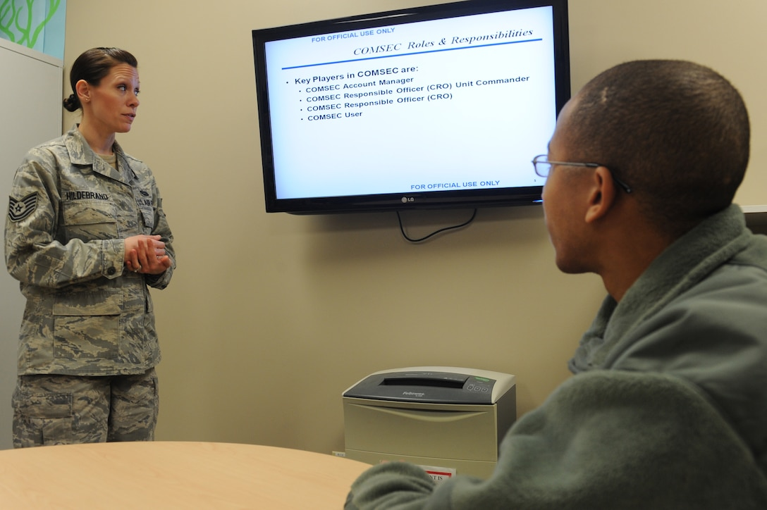 WHITEMAN AIR FORCE BASE, Mo. -- Tech. Sgt. Jessica Hildebrand, 509th Communications Squadron Wing Information Assurance Office NCOIC, reviews training slides with Airman 1st Class Orville Butler, 509th CS WIO, Feb. 11. Every time the B-2 takes off, the WIAO manages 10 different COMSEC items which guarantee the protection of each mission. (U.S. Air Force photo/Airman 1st Class Bryan Crane)