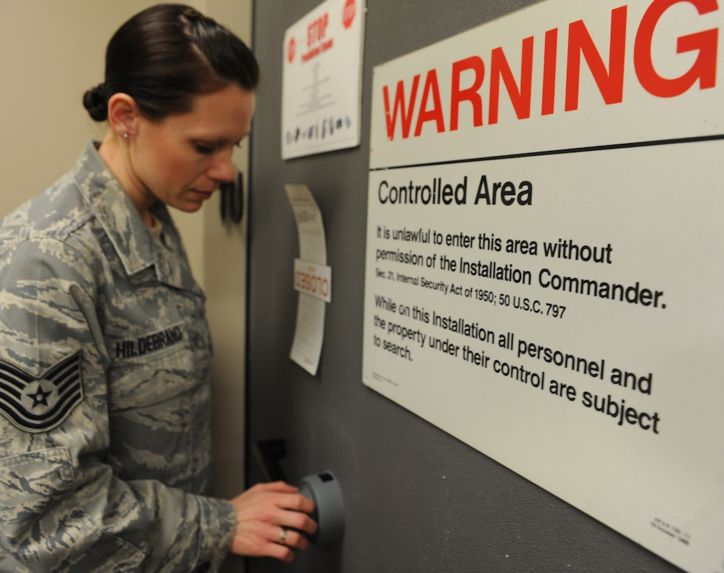 WHITEMAN AIR FORCE BASE, Mo. -- Tech. Sgt Jessica Hildebrand, 509th Communications Squadron Wing Information Assurance Office NCOIC, opens the COMSEC vault door, Feb. 11.  The WIAO shop is a workcenter with five first-term Airmen and only one NCOIC. (U.S. Air Force photo/Airman 1st Class Bryan Crane)