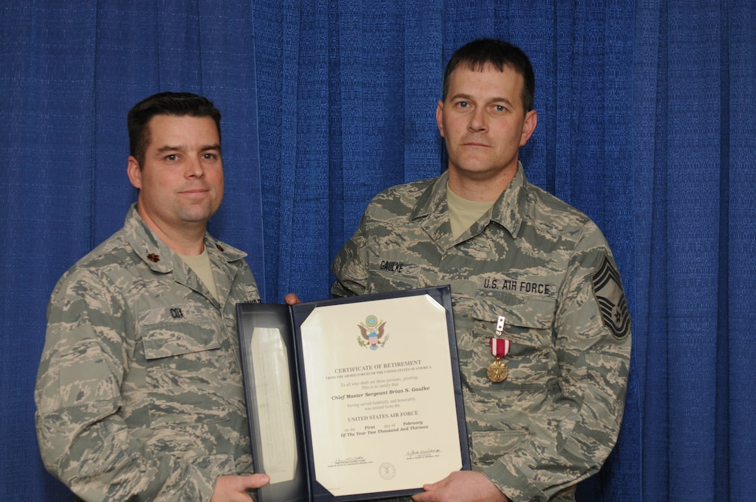 New York Air National Guard Chief Master Sgt. Brian Gaulke (right) receives a Certificate of Retirement from Maj. Patrick Cox, Commander 274th Air Support Operation Squadron, during a 2 February 2013 retirement ceremony held at Hancock Field Air National Guard Base, Syracuse, NY. Chief Gaulke also received a Meritorious Service Medal during the ceremony. Chief Gaulke was one of the first members of the 274th ASOS after it stood up at Hancock Field. (NY Air National Guard photo by Senior Airman Duane Morgan/Released)