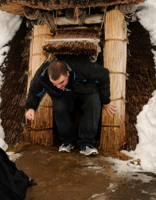 U.S. Air Force Airman 1st Class Christopher Maire, 610th Air Control Flight unit deployment manager, climbs out of a reconstructed pit-dwelling at the Sannai-Maruyama site in Aomori, Japan, Feb. 2, 2013. Pit-dwellings, semi-subterranean structures with circular of oval floor plans, were the most common type of residential buildings during the Jomon period. (U.S. Air Force photo by Airman 1st Class Kenna Jackson)