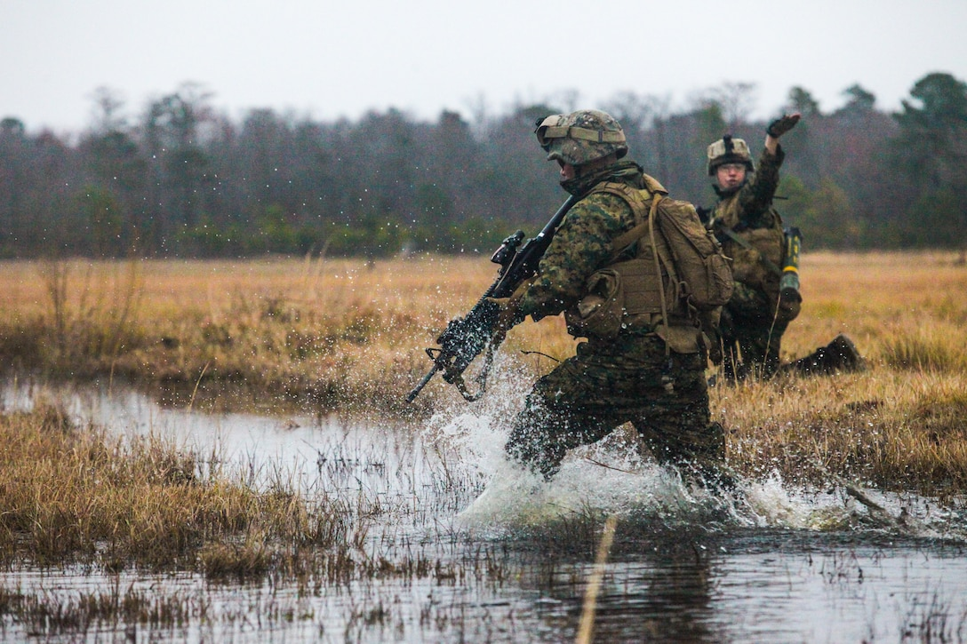 A Marine with Echo Company, 2nd Battalion, 6th Marine Regiment, refuses to allow a puddle of water from keeping him from completing his part of the job. Marines used a strategy known as buddy rushing while taking an enemy machine-gun nest at Shooting Range 6, Feb. 11, 2013. Buddy rushing is when one Marine fires at enemy targets while another Marine runs ahead a few yards before stopping and telling the first Marine to move forward while he fires at targets. The live-fire exercise gave new Marines in the squad an opportunity to learn their job and how the other Marines work together whenever completing a mission. Without unit cohesion the squad will struggle to accomplish mission objectives while on deployment.