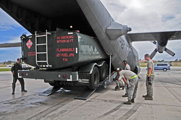 Airmen guide an R-11 refueling truck into the C-130 Hercules on the flightline at Andersen Air Force Base, Guam, Feb. 13. 2013. Andersen Airmen, along with Airmen from units in support of Cope North 13, transported the R-11 refueling truck to Rota island in order to recover a Navy F/A-18 Hornet that diverted due to weather conditions. (U.S. Air Force photo by Airman 1st Class Marianique Santos/Released)