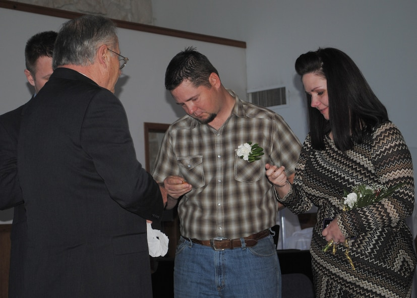 "Dennis Ellingson gives his children a 24-karat gold-plated silver dollar, which symbolizes his ""golden wedding anniversary,"" he said at his vow renewal ceremony.  Dennis married his wife Jacque on Feb. 8, 1963, at the Malmstrom Chapel.  (U.S. Air Force photo/Senior Airman Cortney Paxton)"