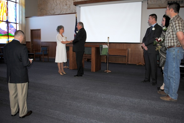 Chaplain (Capt.) Robert Compere, 341st Missile Wing chaplain, far left, officiates Jacque and Dennis Ellingson's vow renewal ceremony Feb. 8 at the base chapel.  Three of the couple's five children flew into Montana to witness the ceremony; pictured from left to right are Army Capt. Edward Ellingson, Alena Ward and Eric Ellingson.  (U.S. Air Force photo/Senior Airman Cortney Paxton)