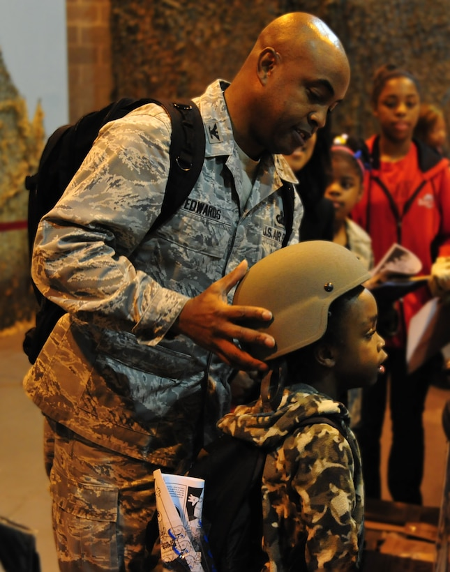 Colonel Trent Edwards, 42nd Air Base Wing Commander, places a helmet on his son Dylan during the inaugural Kids, Spouses and Teachers Understanding Deployment Operations, or KUDOS, SUDOS and TUDOS event, held Saturday on Maxwell. (U.S. Air Force photo by Senior Airman Christopher Stoltz)