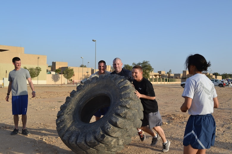 Staff Sgt. Matthew Garrette, Senior Master Sgt. Phillip Monk, Staff Sgt. Stephen Waite, and Airman 1st Class Jessica Navarro represent the 64th Expeditionary Support Squadron, Jan. 25, in the combat obstacle course. Members of the 64th Air Expeditionary Group competed in the annual three-day Commander's Cup in Southwest Asia. Events included M-16A2 assault rifle assembly, carrying sand bags, pushing a HMMWV, a home run derby, firefighter's challenge and others before a final steak cookout. (U.S. Air Force photo/Chief Master Sgt. Jim Dowell)
