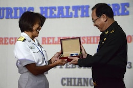 U.S. Navy Rear Adm. Raquel C. Bono, command surgeon, U.S. Pacific Command, left, and Thai Army Lt. Gen. Phanuvich Pumhirun, Royal Thai Army Medical Department, exchanged gifts Feb. 14 at a healthcare symposium in Chiang Mai province, Kingdom of Thailand, during exercise Cobra Gold 2013. The daylong multinational symposium allowed subject matter experts to exchange medical best practices to increase the efficacy of collective efforts to combat dengue fever, melioidosis and other diseases common to Southeast Asia. Exercise Cobra Gold is the largest multinational exercise in the Asia-Pacific region and provides the Kingdom of Thailand, United States, Singapore, Japan, Republic of Korea, Indonesia, Malaysia and observer nations an opportunity to maintain relationships and enhance interoperability.