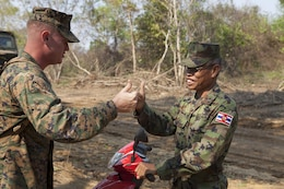 """U.S. Marine Capt. T. Grayson Ernst, left, and Royal Thai Marine Lt. Cmdr. Telone Tutason give each other an international sign of approval Feb. 14 near the base camp of Combat Assault Battalion in Ban Chan Krem, Kingdom of Thailand. The camp is dubbed """"Camp Ivory"""" on account of recently sighted elephants in the area. Thai and U.S. Marines are conducting field training exercises from Feb. 11 to 22 for exercise Cobra Gold 2013, which is a multinational exercise that promotes regional prosperity, security and cooperation among partner militaries. Tutason is the commandant of Camp BCK, and Ernst is a combat engineer officer and current operations director for CAB, 4th Marine Regiment, 3rd Marine Division, III Marine Expeditionary Force."""