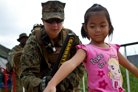 Corporal Elaina M. Rojas, a radio operator with Combat Logistics Battalion 31, 31st Marine Expeditionary Unit, and a native of Kin City, Mo., uses a metal detector to scan a Thai child during a multilateral non-combatant evacuation operation as a part of Cobra Gold 2013 here, Feb. 17. Cobra Gold is the largest multinational exercise in the Asia-Pacific and helps reinforce the foundation and framework for a multinational force to respond rapidly and effectively to regional crises. The 31st MEU is the only continuously forward-deployed MEU and is the Marine Corps' force in readiness in the Asia-Pacific region.