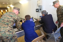 Sgt. Brandon E. Koenig, left, and Sgt. Anthony A. Arriaga, right, assist Teddy Bilirakis, center-left, and Rep. Jeff Miller, center-right, with loading air rifles while displaying a variety of recreational sports available to Marines at the Wounded Warrior Hope and Care Center here Feb. 16.  Koenig and Arriaga are both with Wounded Warrior Battalion West. Miller is the chairman of the House of Veteran Affairs Committee and Bilirakis is the son of the vice chairman.