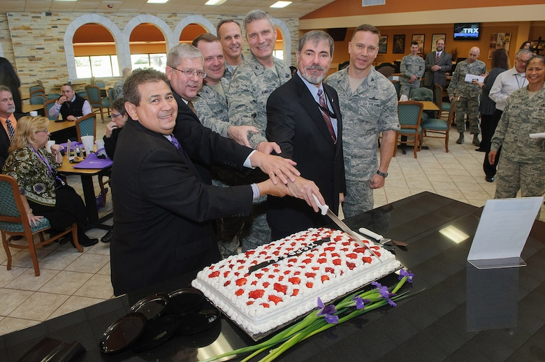 A cake cutting by committee is lead by civilians (left to right) Rick Aleman, Selrico Services president; Ken Williams, Air Force Intelligence, Surveillance and Reconnaissance Agency director of staff and Greg Radabaugh, Joint Information Operation Warfare Center director plus others, during the soft opening Feb. 13 of the new Gott Commons Community Center. The Commons official grand opening was Feb. 19 on Joint Base San Antonio – Lackland's Security Hill. (U.S. Air Force photo by William Belcher)