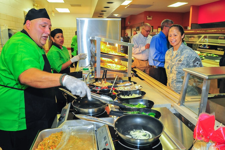 Air Force Intelligence, Surveillance and Reconnaissance Agency Command Chief Master Sgt. Arleen Heath eagerly waits for her stir fry order at the new Gott Commons Community Center. The Commons grand opening was Feb. 19 on Joint Base San Antonio – Lackland's Security Hill. (U.S. Air Force photo by William Belcher)
