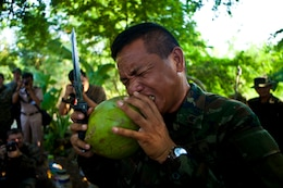 Chief Petty Officer First Class Veing Pimsorn, a Thai reconnaissance Marine, uses his teeth to demonstrate how to skin a coconut during a jungle survival class taught to Marines and Sailors of the 31st Marine Expeditionary Unit by Royal Thai Marines as a part of Cobra Gold 2013 here, Feb. 20. The class detailed ways to find direction in the jungle, how to identify edible plants and animals, and how to prepare food fit to eat.  Cobra Gold demonstrates the resolve of the U.S. and participating nations to increase interoperability, and promote security and peace throughout the Asia-Pacific region. The 31st MEU is the only continuously forward-deployed MEU and is the Marine Corps' force in readiness in the Asia-Pacific region.