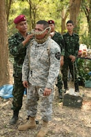 Royal Thai Army Special Forces Master Sgt. 1st Class Thong Nimnuan, left, places a python on U.S. Army Sgt. Daniel A. Hernandez during a jungle survival training class Feb. 17 at Camp Akatosrot, Phitsanulok province, Kingdom of Thailand, as part of exercise Cobra Gold 2013. Thai soldiers attending the training are with 7th Regiment, 7th Division, 3rd Region, Royal Thai Army. Hernandez, an infantryman, and other U.S. soldiers are with Baker Company, 2nd Battalion, 9th Infantry Regiment, 1st Armored Brigade Combat Team, 2nd Infantry Division. U.S. involvement in CG 13 demonstrates commitment to building military-to-military interoperability with participating nations and to supporting peace and stability in the region.