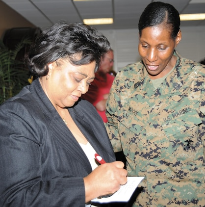 Guest speaker Shirley Sherrod, left, signs an autograph for Master Gunnery Sgt. Carlotta Moore at the Black History Month luncheon here, Feb. 12.