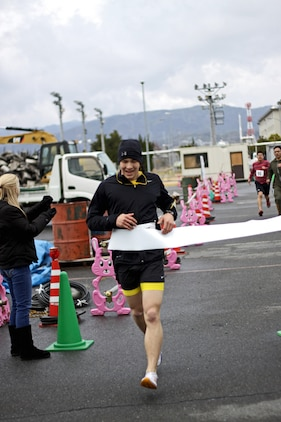 Michael Gutschmidt, Gokukan two and a half kilometer Fun Run participant and overall winner, crosses the finish line for the event, which took place on the seawall behind the IronWorks Gym here, Feb. 15, 2013. The race path guided participants from the seawall ramp beside the obstacle course to the back of the gym, then doubling back toward the Monzen Bridge twice before racing down the ramp and finishing inside the parking lot by the obstacle course.
