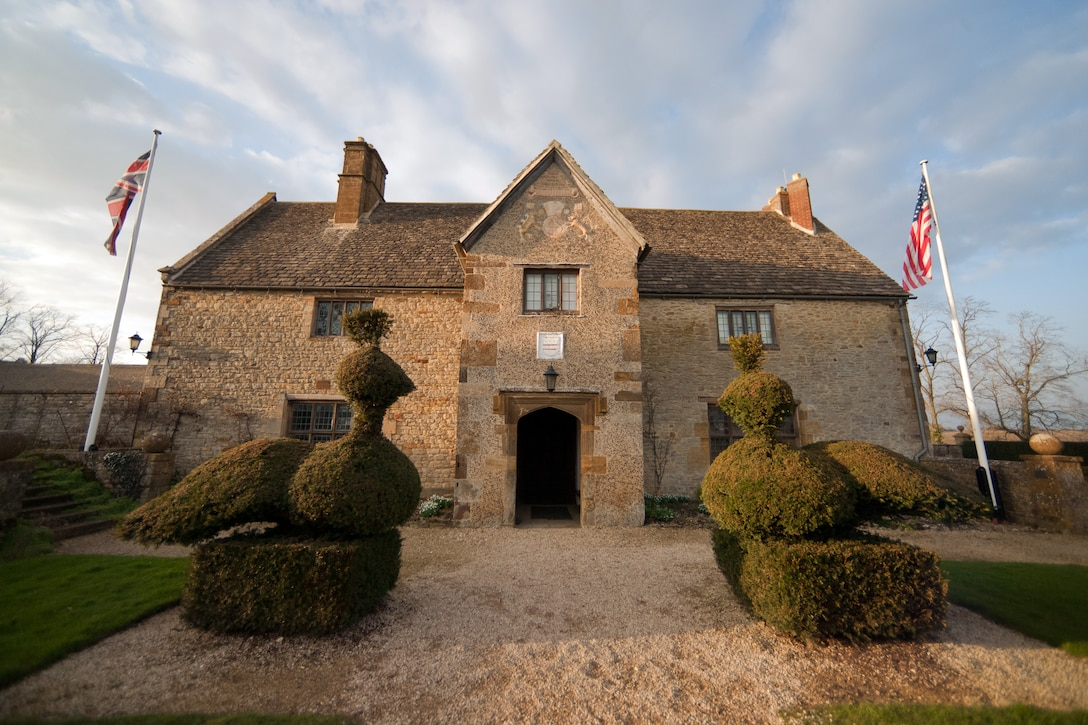 SULGRAVE, United Kingdom – Outside view of Sulgrave Manor in Sulgrave, United Kingdom. Sulgrave Manor is famous for having been the ancestral home of George Washington. The house, built in the mid-1500s, was built of local limestone, with a wide south frontage, a kitchen and buttery, a Great Hall, and above it a Great Chamber and two smaller private chambers. All these parts survive and can be seen today. The Great Hall has a stone floor, and its Tudor fireplace contains a salt cupboard carved with the initials of Lawrence Washington, the builder. Lawrence Washington, a Northampton wool-trader, is the great-great-great-great-great grandfather of George Washington. The Washington's held the house for more than one hundred years. (U.S. Air Force photo by Staff Sgt. Brian Stives)