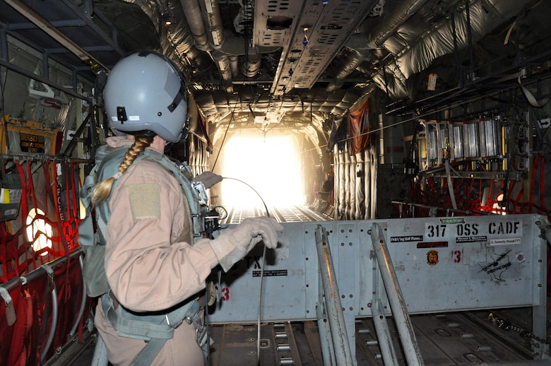 Master Sgt. Tracey Smith, 772nd Expeditionary Airlift Squadron loadmaster, releases an airdrop, containing food and fuel for troops from a C-130J Feb. 14, 2013, above southern Afghanistan. Smith is one of many deployed 317th Airlift Group Airmen from Dyess Air Force Base, Texas, currently assigned to the 772nd EAS. (U.S. Air Force photo by Capt. Tristan Hinderliter/Released)