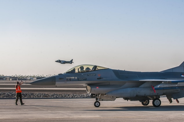An F-16 from the Royal Netherlands Air Force taxis into a refueling station while AV-8B Harriers of Marine Attack Squadron 214 take off from Marine Corps Air Station Yuma, Ariz. Feb. 7, 2013. The RNLAF detachment is conducting aviation training in Yuma for three weeks before returning to the Netherlands.