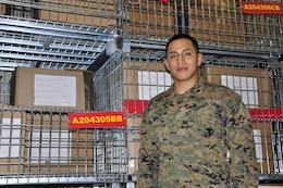 Cpl. Michael Ramirez, Headquarters and Service Battalion's Noncommissioned Officer of the 4th Quarter and Noncommissioned Officer of the Year, stands in front of one of the bins in Security Battalion's warehouse. Ramirez is currently the Security Bn. warehouse chief.