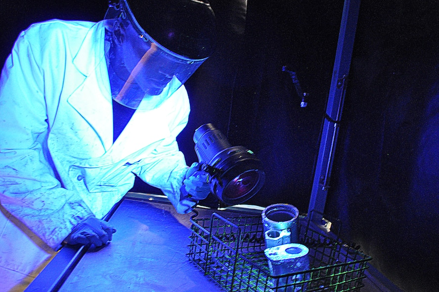 Tech. Sgt. Steven Smith, 507th Air Refueling Wing non-destructive inspection lab shop chief inspects parts off a KC-135 Stratotanker during the final stage of a penetrant test.  The black light shows any cracks that are not visible to the human eye.  The NDI lab inspects about 300 parts either in the lab or with their portable units every month.  (U.S. Air Force photo by Senior Airman Mark Hybers)