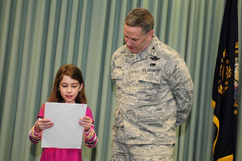Zoe Selig, an elementary student from Moharimet Elementary School in Madbury, N.H, reads a letter of support for basing the Boeing KC-46A air refueling tanker at Pease Air National Guard Base to Col. Peter Sullivan, 157th Air Refueling Wing Vice Commander, Pease Air National Guard Base, N.H., Feb 20, 2013.  The letter was signed by 59 students. (National Guard photo by Tech. Sgt. Aaron P. Vezeau/Released)