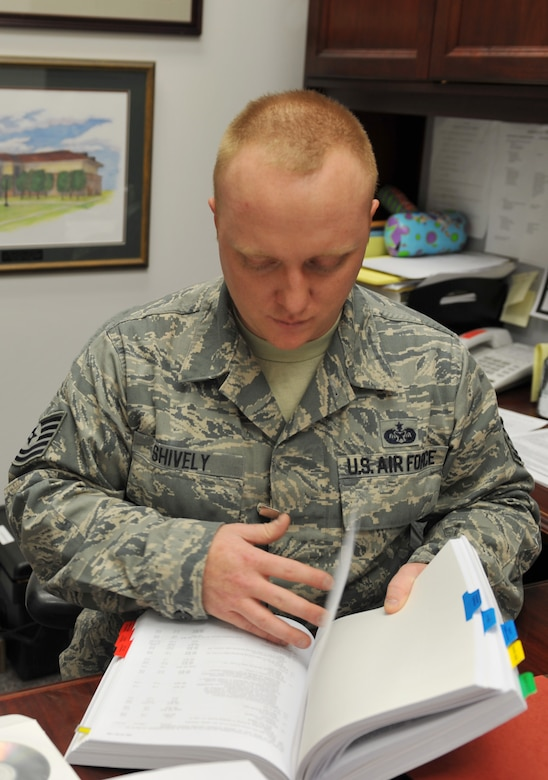 WHITEMAN AIR FORCE BASE, Mo. -- Tech. Sgt. Matthew Shively, 509th Bomb Wing Legal Military Justice NCO in charge, does research on legal issues during his shift at the 509th Bomb Wing Legal Office, Feb. 19, 2013. Shively refers to the book often to prepare for upcoming cases and real-world issues. (U.S. Air Force photo/Heidi Hunt)