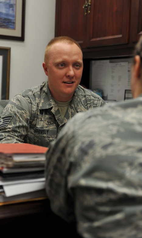 WHITEMAN AIR FORCE BASE, Mo. -- Tech. Sgt. Matthew Shively, 509th Bomb Wing Legal Military Justice NCO in charge, speaks with a Team Whiteman member during his shift at the Whiteman AFB Legal Office. Shively's legal experience and leadership allows him to ensure mission readiness and military discipline. (U.S. Air Force photo/Heidi Hunt)