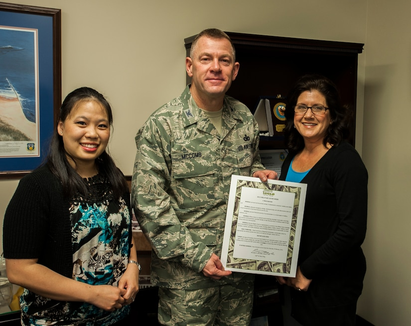 Colonel Richard McComb, Joint Base Charleston commander, presents the seventh annual Military Saves Campaign pledge to (left) Suerjee Lee, Joint Base Charleston – Weapons Station lead personal financial educator,  and Barbara  Lang, Community Readiness Consultant and Certified Financial counselor Feb. 13, 2013, at Joint Base Charleston – Air Base, S.C. Military Saves Week is Feb. 25 through March 2, 2013. (U.S. Air Force photo / Airman 1st Class Tom Brading)