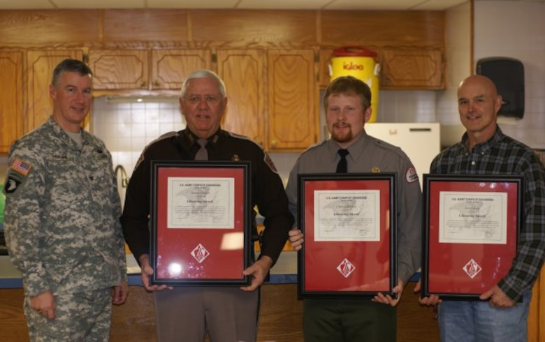 From left to right, Col. Michael Teague, Tulsa District commander presents lifesaving awards to Trooper Danny Choate, Ranger Chris Gilliland and Ranger Eric Fassio. The three were recognized for their efforts to save two individuals that were stranded in the river below Eufaula Dam last summer.