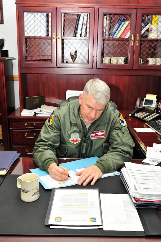 U.S. Air Force Col Philip Wielhouwer, 355th Operations Group commander, signs documents in his office on Davis-Monthan Air Force Base, Ariz., Feb. 21, 2013. The 355th OG consists of five squadrons and over 300 personnel.(U.S. Photo by Airman 1st Class Josh Slavin/Released)