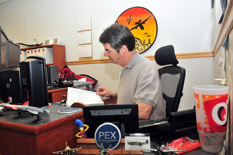 Paul Richard, 355th Operations Group Patriot Excalibur software administrator, reviews a folder on Davis-Monthan Air Force Base, Ariz., Feb 21, 2013. Patriot Excalibur software enables full-scale deployment of battle-ready units. (U.S. Photo by Airman 1st Class Josh Slavin/Released)