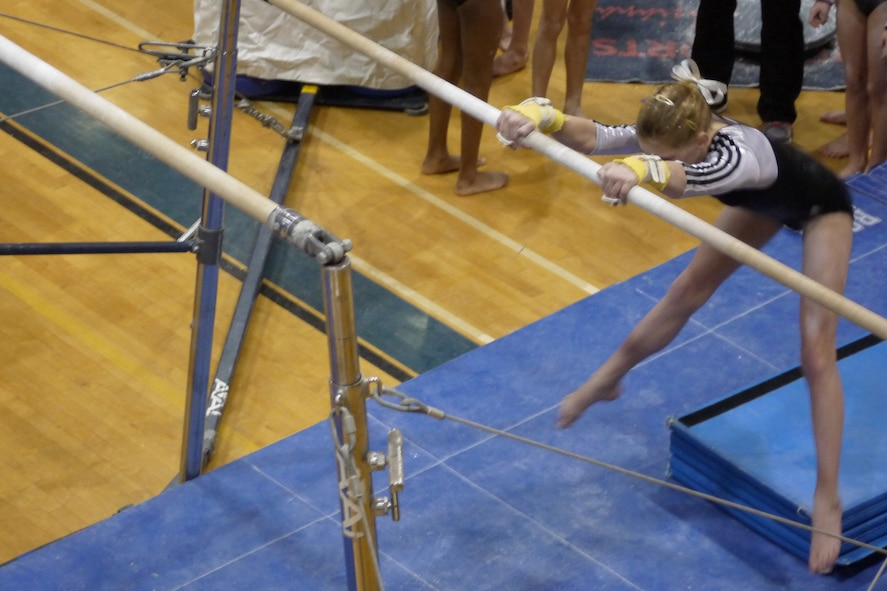 Renae Suberly, daughter of Maj. Michael Suberly, 8th Air Force Office of the Staff Judge Advocate, and Maj. Michelle Suberly, Air Force Global Strike Command Office of the Staff Judge Advocate, competes on the uneven bars during the Emerald Classic Feb 16-17 in Cabot, Ark. Suberly her team to a first-place finish in the competition.