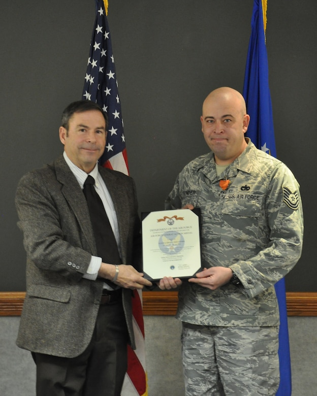 "Tech. Sgt. John Fender, 90th Missile Wing Plans and Programs, and Barry Kistler, 90th MW director of staff, hold Fender's Air Force Combat Action Medal citation Feb. 14 in the Wing Conference Room on F. E. Warren Air Force Base, Wyo. Fender was awarded the AFCAM for ""active participation in combat, having been under direct and hostile fire or physically engaging hostile forces with direct and lethal fire, in connection with military operations."" Fender's actions were in support of Operation Enduring Freedom from Aug. 14, 2004 to March 6, 2005. (U.S. Air Force Photo by Staff Sgt. Torri Savarese)"